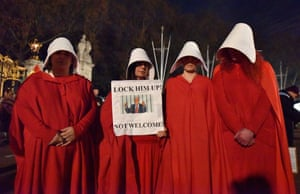 Anti-Trump protesters gather outside Buckingham Palace dressed as handmaids from Margaret Atwood's Handmaid's Tale