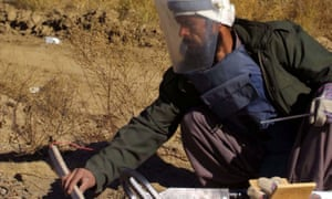 An Afghan landmine detection and disposal worker  at work near a road near Kabul