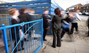 A teacher supervises children leaving a secondary school.