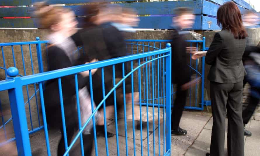 A teacher supervises children leaving school