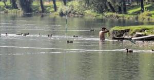 A man washes himself in the River Una in Bihać