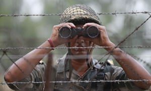 An Indian border security force soldier looks for potential threats, near Jammu in India.