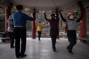 Pensioners dancing to folk music beneath a pavillion in the city park