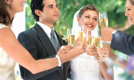 Bride, groom and wedding guests toasting with champagne