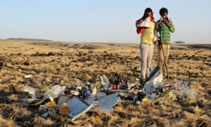 Two local boys examine debris gathered by workers during the continuing recovery efforts at the crash site in Bishoftu, Ethiopia, in March.