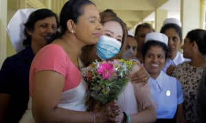 Sri Lankan health minister Pavithra Wanniarachchi, left, greets Chinese woman Luo Yan, who had the first confirmed case of coronavirus in Sri Lanka as she leaves the National Institute of Infectious Diseases in Colombo in February 2020