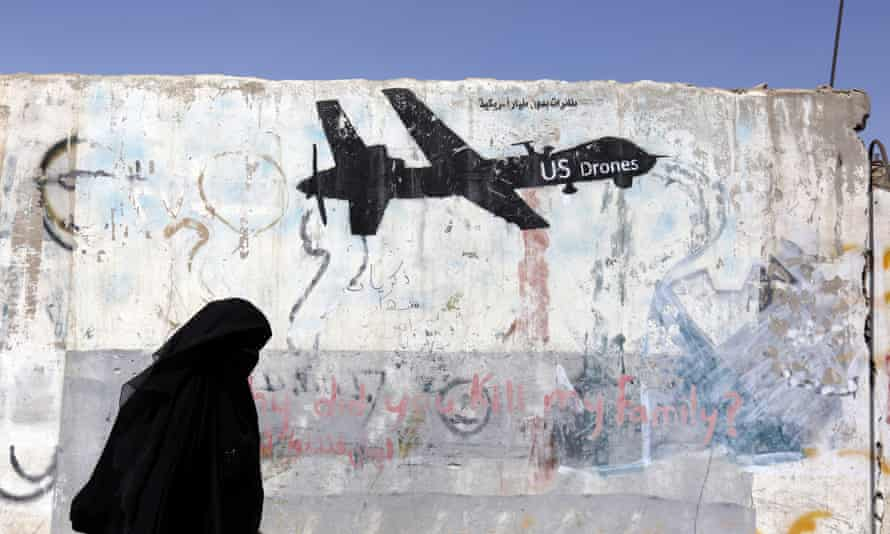 A woman walks past a graffiti depicting a US drone in Sana'a, Yemen. US drone strikes have been used in countries such as Yemen and Somalia, designated by the US as areas of 'active hostilities'.
