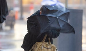 Pedestrian struggles against wind with umbrella.