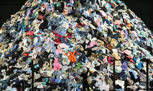 A woman photographs French artist Christain Boltanski's 'No Man's Land', composed of around 30 tonnes of discarded clothing.