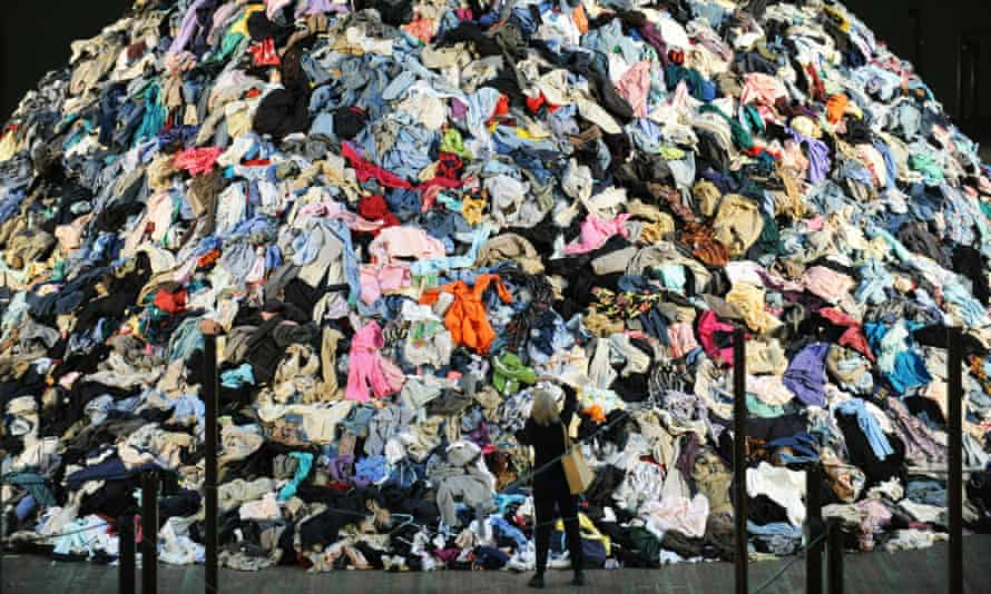 Woman standing by giant pile of clothes