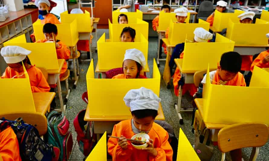 Schoolchildren at desks with plastic partitions