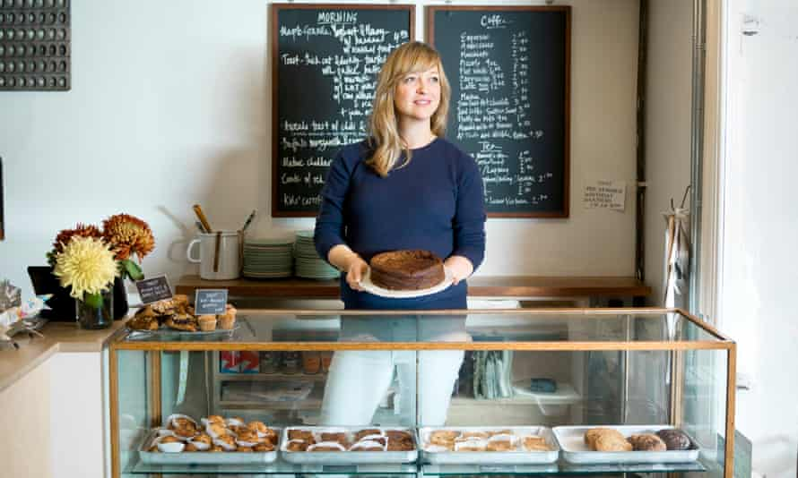 Claire Ptak in her shop Violet Bakery holding a cake.