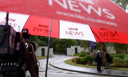 A BBC umbrella covers a TV camera outside the Berkshire estate where Sir Cliff Richard has an apartment.