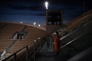 Ground staff members stand guard among the empty seats at the Suzanne Lenglen court in the evening of day two of the 2020 French Open in Paris.