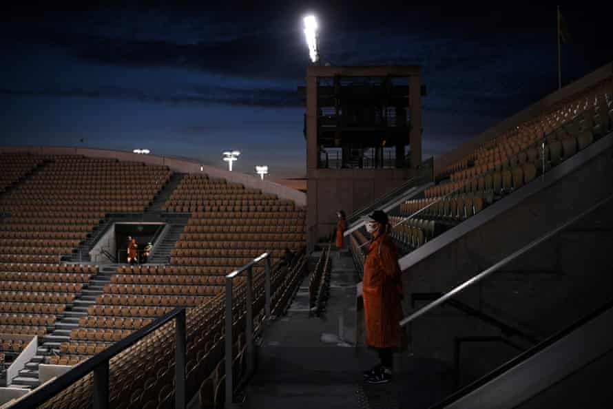 Ground staff stand guard among empty seats at the Suzanne Lenglen court during day two of the French Open in Paris on 28 September.