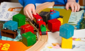 A child playing with toy train and blocks