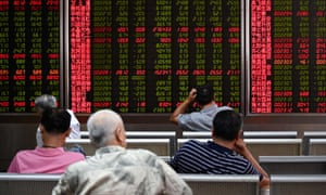 Screens showing stock market movements at a securities company in Beijing.
