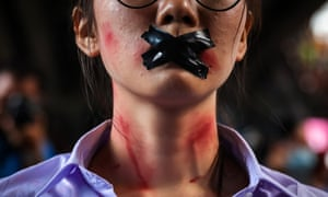 A protester with makeup and tape over her mouth protests alleged sexual assault in Thai classrooms.
