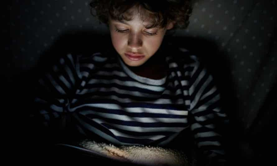 Young boy on sofa in dark room watching touchpad illuminated with screen light
