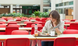 A student eats alone in a cafeteria.
