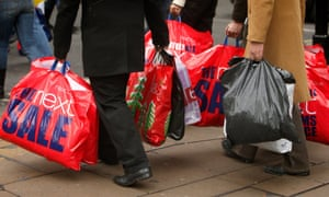 shoppers carry 'sale' bags on the high street