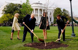 Trump and Macron shovel dirt on to a freshly planted oak sapling that Macron brought with him as a symbol of friendship