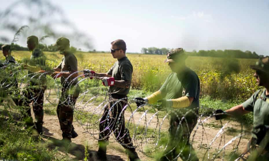Soldiers set up a razor-wire fence to keep out refugees, on Hungary's southern border with Croatia.