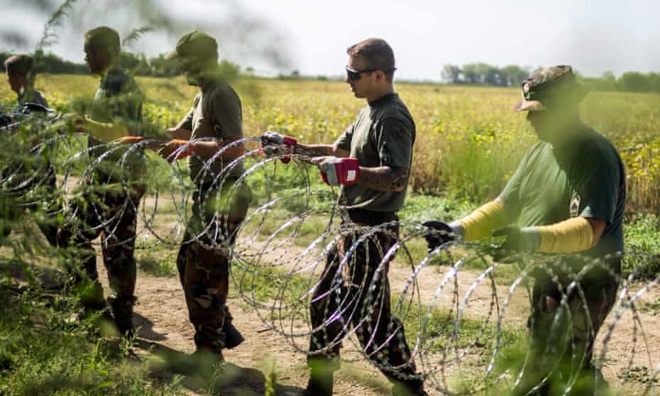 Hungarian soldiers set up razor wire on the border with Croatia