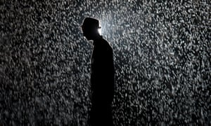 A man poses for pictures as he walks through Rain Room, an installation at the Barbican in London, in 2012.