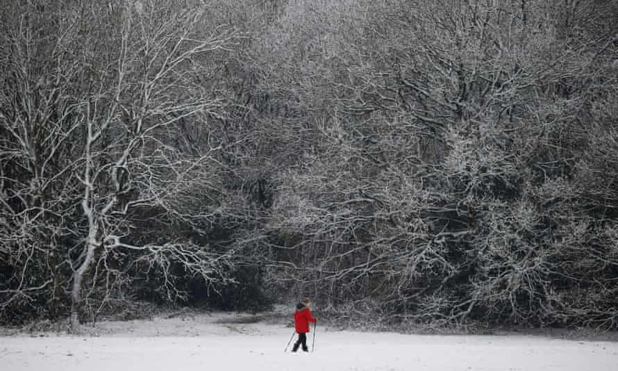 A woman walks across a snow-covered park in Knutsford