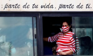 زنی با ماسک صورت از 16 مارس 2021 در هاوانا ، کوبا از پنجره اتوبوس نگاه می کند.