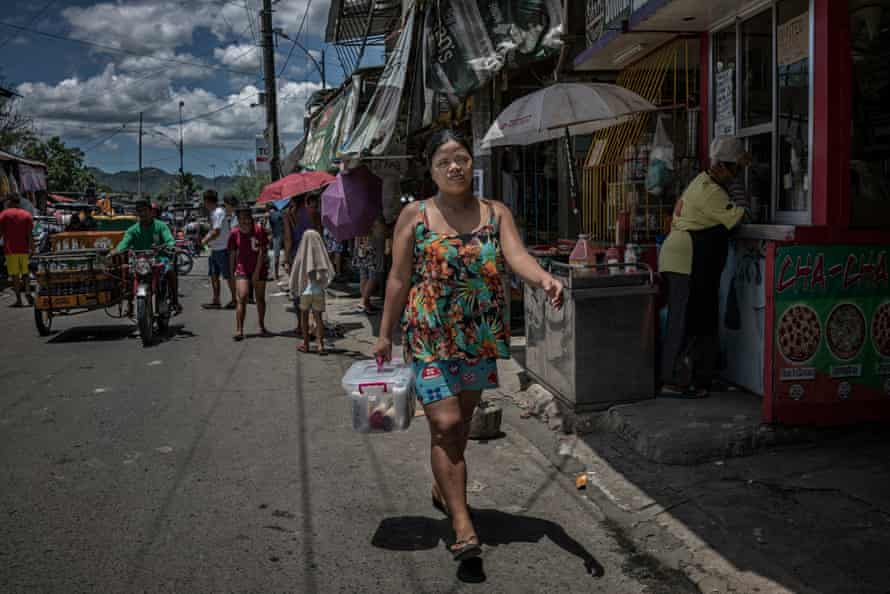 Rhoda, a widow who is raising seven children after her husband was killed in an extrajudicial killing, walks through the streets of Payatas to deliver a sale of an Avon product, which she started selling door to door in January 2018.
