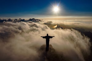 Rio de Janeiro, Brazil. The sun rises in front of the Christ the Redeemer statue, which is undergoing restoration to ensure that it looks its best for the returning tourists