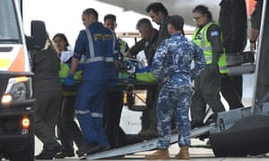 An evacuated survivor of the Whaakaari eruption is transferred to an ambulance at Sydney airport.