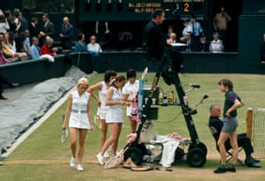 The players in a 1967 women's doubles match take a drinks break between games with no seats available for the players