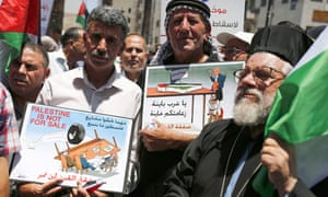 Palestinian demonstrators carry caricatures, during a protest against the US-led Peace to Prosperity conference that opens tomorrow in Bahrain, in the Israeli-occupied West Bank city of Ramallah on Monday.