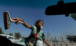An Iraqi girl cleans the windscreen of a car at traffic lights in the capital.