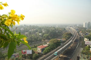 A Kochi Metro train travels along an elevated track in the Aluva-Pulinchodu area of Kochi