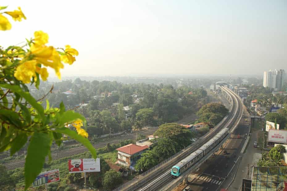A Kochi Metro train travels along an elevated track in the Aluva-Pulinchodu area of Kochi