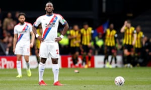 Crystal Palace's Michy Batshuayi looks dejected as Watford's Andre Gray celebrates scoring their second goal with teammates.