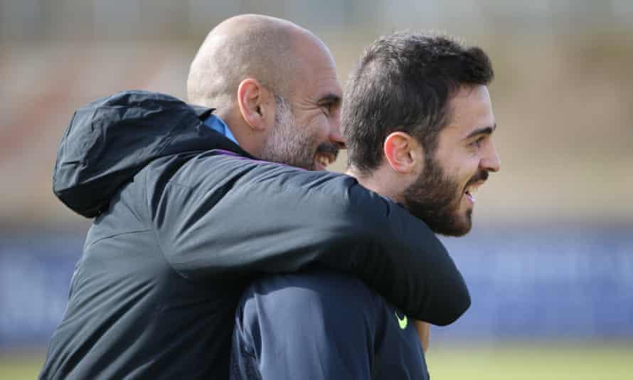 Pep Guardiola (left) embraces Bernardo Silva (right).