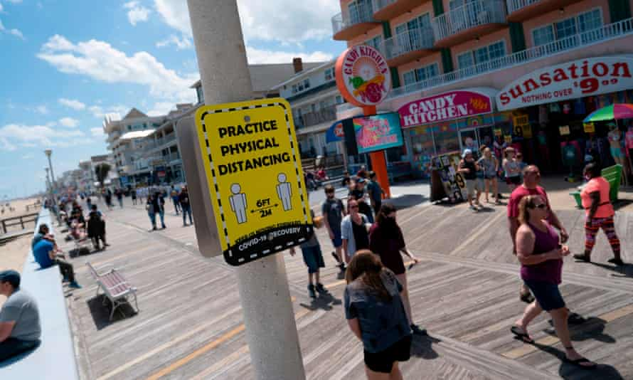 People walk past a sign advising social distancing on the boardwalk in Ocean City, Maryland.