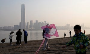 A man prepares to fly a kite as people walk along the coast of the Yangtze River at Jiangtan park on December 5, 2020 in Wuhan, Hubei province, China.