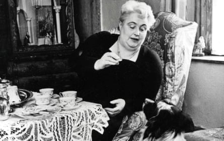 Margery Allingham, feeding one of her dogs at home.