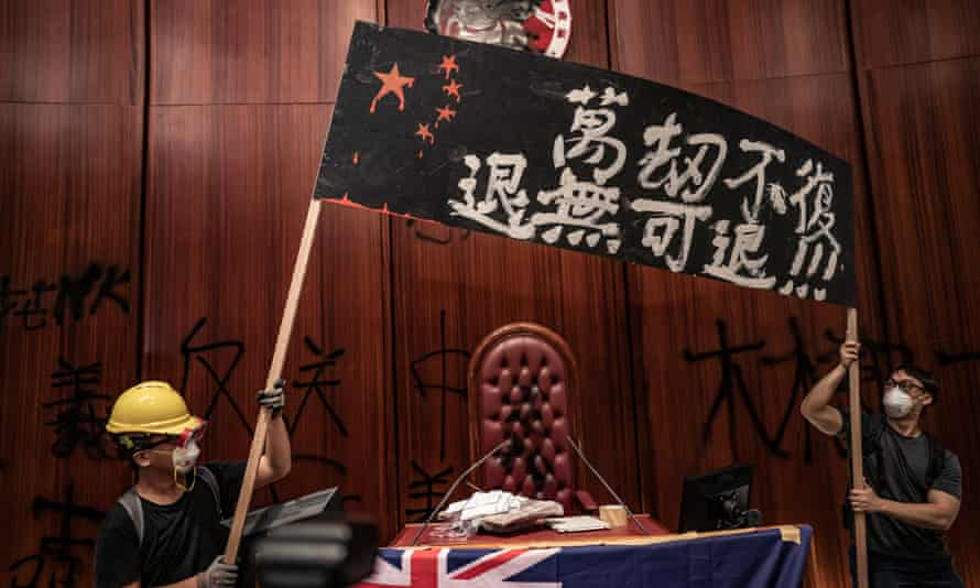 Protesters put up a banner after they broke into the parliament chamber of the government headquarters in Hong Kong
