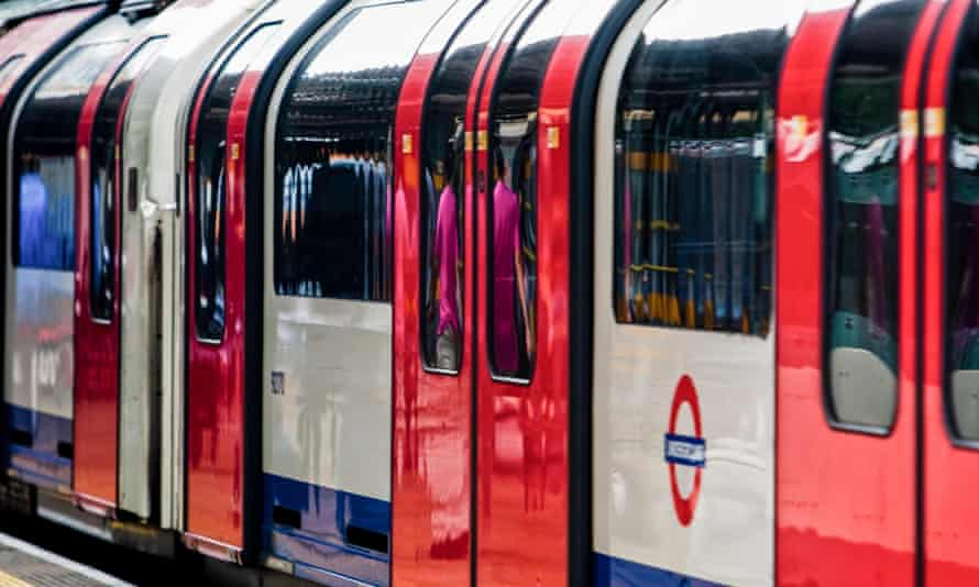 A Central line tube train stopped at a station.
