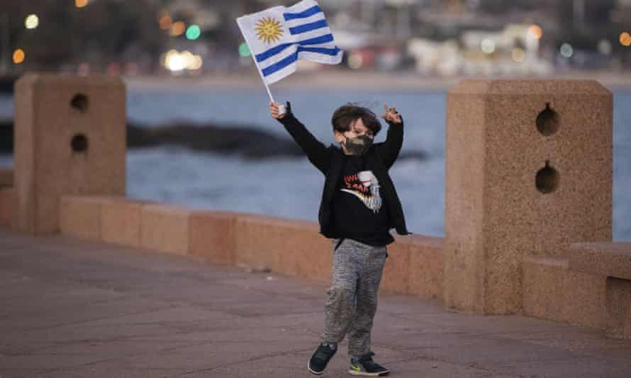A boy wearing a protective face mask waves a Uruguayan national flag in Montevideo, Uruguay.