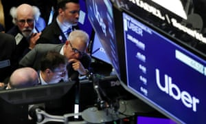 Traders gather at post where Uber holds its IPO on the floor of the New York Stock Exchange