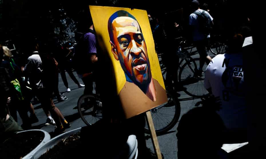 A person holds a portrait of George Floyd at the steps of Brooklyn Borough Hall during a Black Lives Matter protest in June 2020.