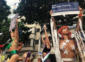 Stilt performers at Mulheres Rodadas, one holding up a Marielle Franco street sign.